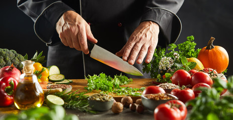 Man chopping herb leaves on cutting board