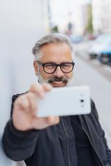 Man posing for a selfie in an urban street