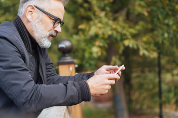 älterer mann schreibt draußen eine sms