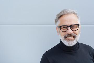älterer mann mit brille lacht in die kamera
