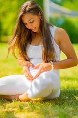 Beautiful pregnant woman sitting outdoor making hand heart gesture on belly