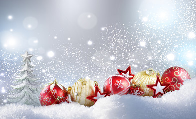 Christmas colorful layout. Christmas golden balls, red stars and Christmas tree on snow in winter snowdrift on silvery sparkling background with falling snow and copy space.