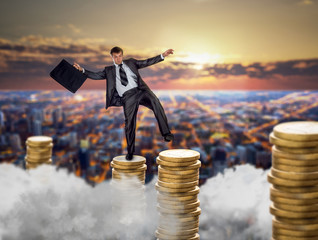 Businessman on stacks of coins, financial balance