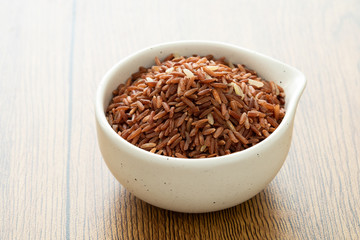 brown rice for healthy white bowl on wood background
