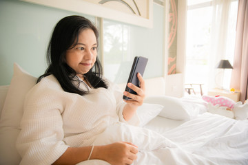 Woman sitting on white bed looking smartphone with frustration or angry