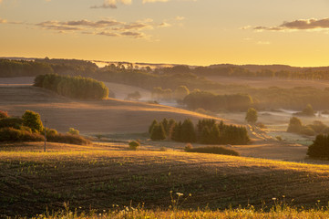 fields and meadows on a magnificent misty and sunny morning. landscape picture resembling Italian Tuscany. Autumn, Poland, Drawsko Lake District