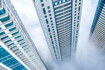 Cityscape view from above looking down a skyscraper on a foggy day. Fear of heights, vertical living concept