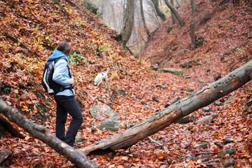 Young wman hiking through an autumn forest with her dog.