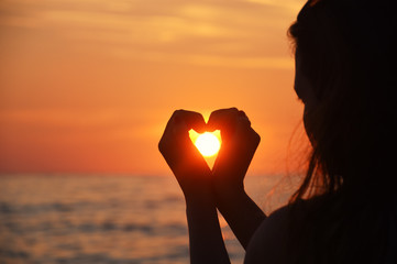 Woman making heart with her hands against the sun at the beach. Love concept heart and sun silhouette