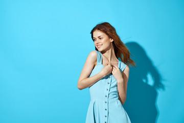 happy woman in a blue sundress looks away