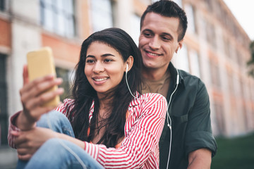 Music for two. Cheerful relaxed young woman sharing earphones with her positive beloved man and smiling while looking at the screen of her modern device