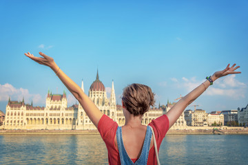 Wall Mural - Happy youg girl raising arms in from of Budapest parliament, Hungary