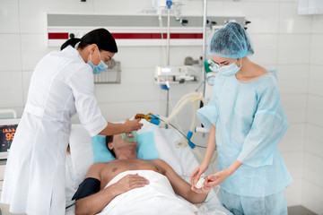 Medical team. Unconscious middle aged man lying in hospital bed and getting mechanical ventilation. Young assistant in sterile uniform holding man hand with pulse oximeter on finger