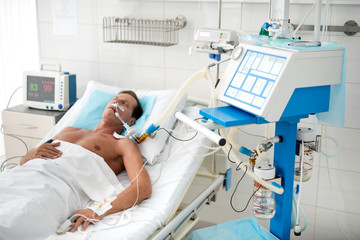 Portrait of unconscious middle aged man on mechanical ventilator lying in hospital bed under white sheets