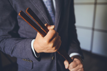 Man with leather tawse. Strict headmaster with tawse. Corporal punishment in school. BDSM concept. Adult role game concept. strict school teacher with tawse