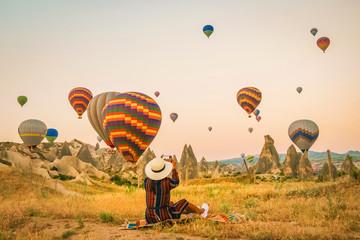 Turkey balloons Cappadocia Goreme Kapadokya , Sunrise in the mountains of Capadocia, happy young woman watching sunrise