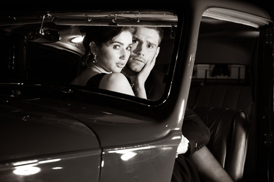 Good looking sexy couple, handsome man in suit, beautiful woman in red dress, are discovered embracing in vintage car