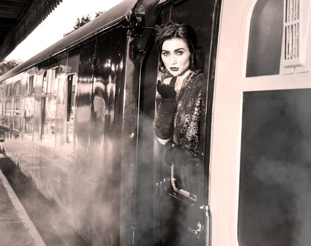 Woman dressed in vintage evening dress leaning out of train window and blowing a kiss