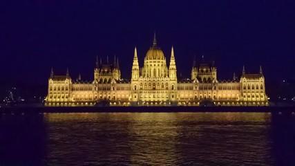 Wall Mural - Budapest parliament illuminated at night and Danube river; Hungary - Video HD