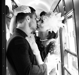 Sexy vintage couple kissing and holding each other passionately in corridor of train