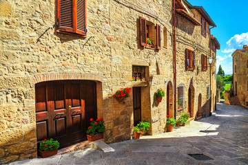 Rustic stone houses decorated with colorful flowers, Monticchiello, Tuscany, Italy