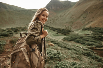 Confident hiker. Positive experienced traveler feeling happy in the mountains and smiling while carrying backpack