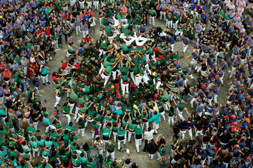 """Members of group """"Castellers de Sant Cugat"""" fold down a human tower called """"castell"""" during a biannual human tower competition in Tarragona"""