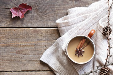 Coffee or tea with milk and spices. Rustic autumn background. Overhead view, copy space