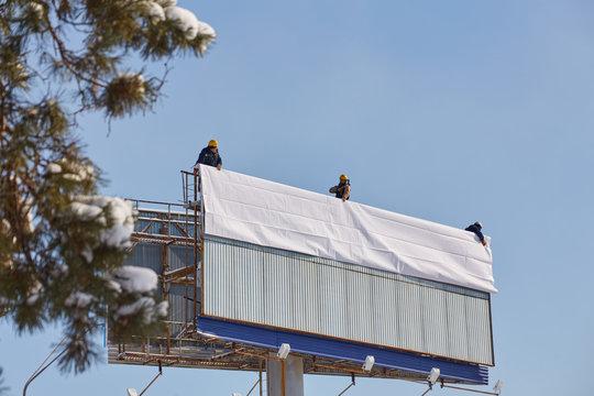 Worker prepares billboard to installing new advertisement.
