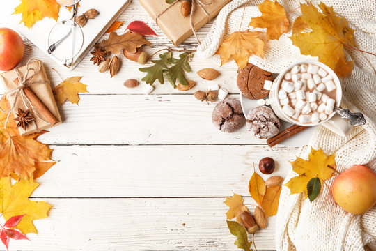 Autumn composition. Dark scarf, a cup of cocoa with marshmallows, autumn dry leaves on a white wooden table. Top view. Copy space