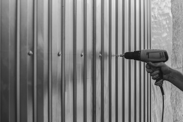 a man screws sheets of galvanized metal with an electric screwdriver, black and white photo