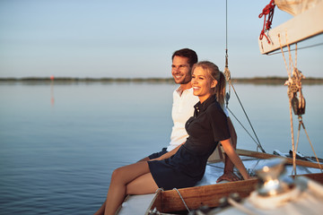 Smiling young couple enjoying an afternoon on their yacht Wall mural