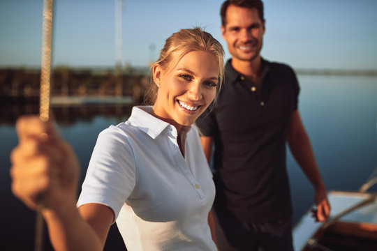 Smiling young couple standing on the deck of their yacht