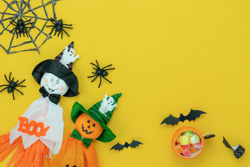 Table top view aerial image of decoration Happy Halloween day background concept.Flat lay accessories essential object to party the cute doll & sweet candy on yellow paper.Space for creative design.