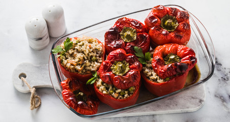banner of ready baked stuffed peppers in a glass baking dish on white marble table. healthy vegan cuisine for the whole family. comfort food