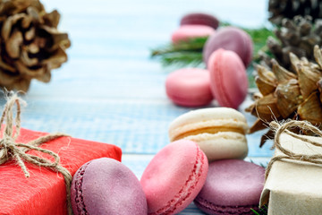 Sweet macarons, gifts and fir cones and on a blue background. Christmas background. New Year's composition.