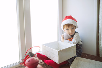 Cute little boy in santa hat sitting on window sill and look at camera in christmas day. Space for image on window. Copy Space