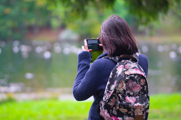 girl photographs nature lake on a smartphone. standing back. walk trip to new places