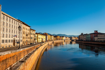 Beautiful morning on the river in Pisa, with small houses and blue sky