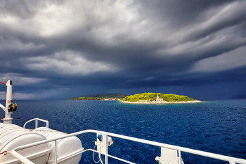 Cruise liner at the sea and dramatic storm clouds over island , Croatia