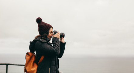 Woman traveler takes pictures of the landscape