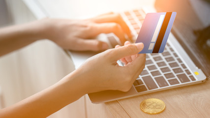 Hand holding credit card and using laptop. Online shopping concept.