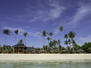 Landscape shot of a beach with huts and palm trees in the background