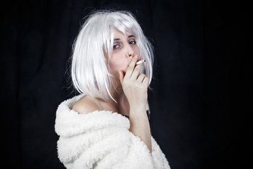 Attractive young woman in costume smoking cigar and looking at camera while standing on black background