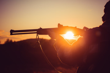 Trigger of the shotgun. Rifle Hunter Silhouetted in Beautiful Sunset. Silhouette of the hunter.