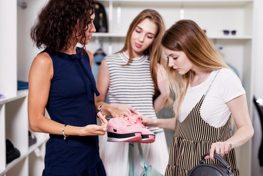Portrait of smiling young woman holding a pair of new pink sneakers looking happy with her purchase at boutique