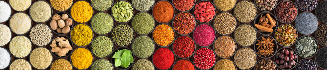 Fototapete - Various spices and herbs as a background. Colorful condiments in cups, top view