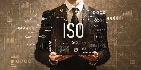 ISO with businessman holding a tablet computer on a dark vintage background