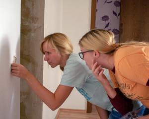 Renovierungskonzept: zwei junge Frauen beim ausbau einer Steckdose