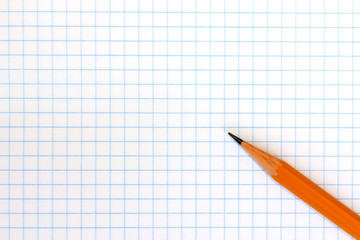 A wooden yellow pencil on checkered exercise book paper with copy space